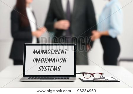 Concept of management information systems. Workplace with laptop and people on background