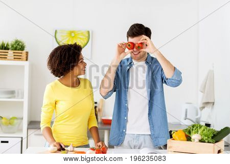 people, healthy eating and international concept - happy couple cooking food and having fun at home kitchen