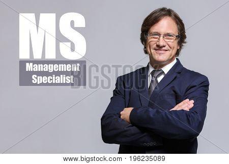 Concept of management specialist. Mature businessman on grey background