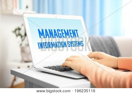 Concept of management information systems. Woman working with laptop at table, closeup