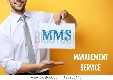 Concept of management service. Young businessman holding paper with abbreviation MMS on yellow background