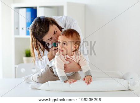 medicine, healthcare, pediatry and people concept - otolaryngologist or doctor checking baby ear with otoscope and young woman at clinic