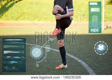 sport, football training and technology - soccer player stretching leg on field