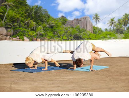 fitness, sport, yoga, people and healthy lifestyle concept - couple making side crane pose on mat over tropical beach background