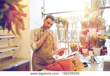 people, business, technology, sale and floristry and concept - florist man with tablet pc computer thinking at flower shop counter
