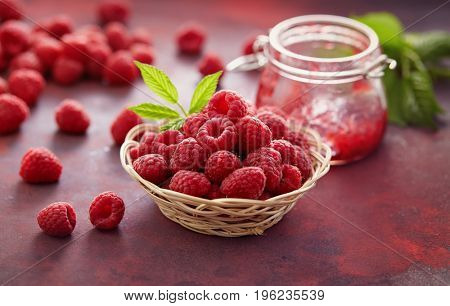 Fresh raspberries and a jar of raspberry jam.