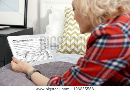 Senior woman using tablet for filling in individual income tax return form on bed