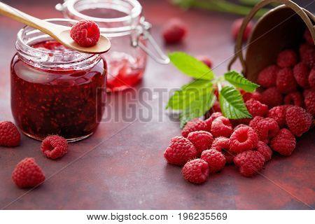 Fresh raspberries and a jar of raspberry jam.