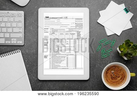 Workplace with office stationery. Tablet with individual income tax return form on screen