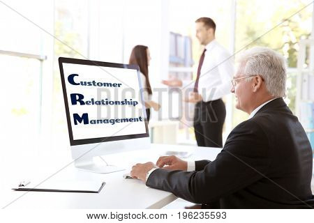Concept of customer relationship management. Senior man working with computer in office