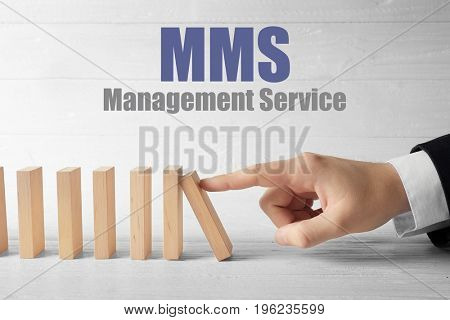 Concept of management service. Man pushing dominoes on wooden background, closeup