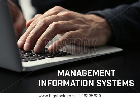 Concept of management information systems. Man working with laptop at table, closeup