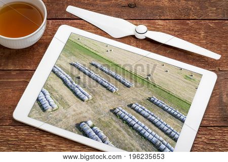 hay bales in Nebraska Sandhills, reviewing aerial image on a digital tablet with a cup of tea