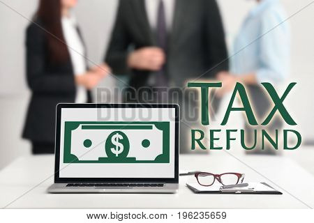 Workplace with laptop and business people on background. Tax refund concept
