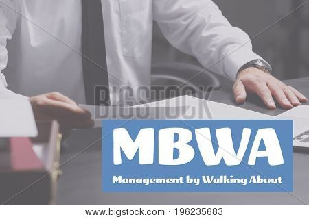 Concept of management by walking about. Businessman working with documents at table, closeup