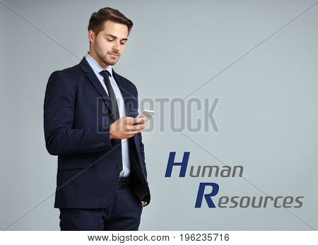 Concept of human resources management. Young businessman with phone on color background