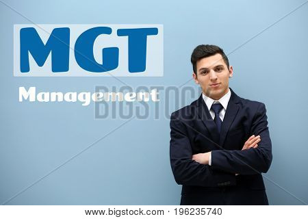 Management concept. Young businessman on color background