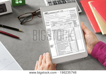 Woman using tablet for filling in individual income tax return form at table