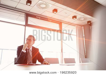 Mature businessman listening to meeting in board room