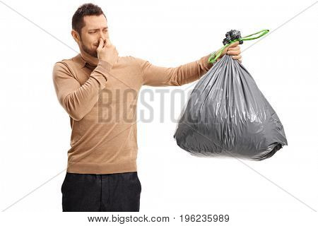 Young man holding a stinky garbage bag and covering his nose isolated on white background