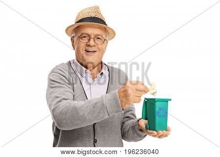 Senior throwing a piece of garbage in a small recycling bin isolated on white background