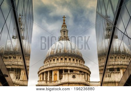 The iconic dome of St Paul's Cathedral in the city of London. The dome is framed by the glass exterior of two modern buildings creating a triptych with the reflections.