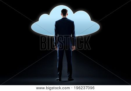 business, people and technology concept - businessman in suit looking at virtual cloud hologram over black background