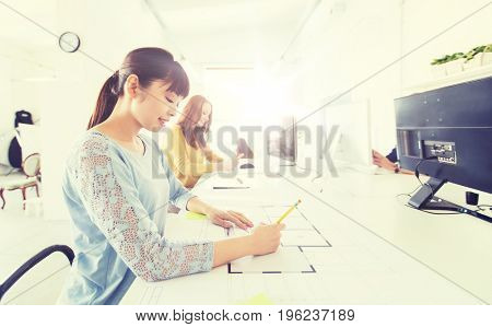 business, startup and people concept - asian architect or creative female office worker with ruler and pencil drawing on blueprint