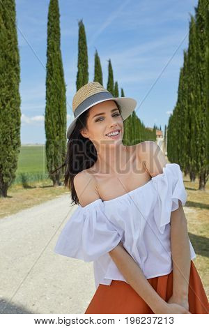 Woman is walking along the road among the fields and a typical Tuscan landscape behind her.