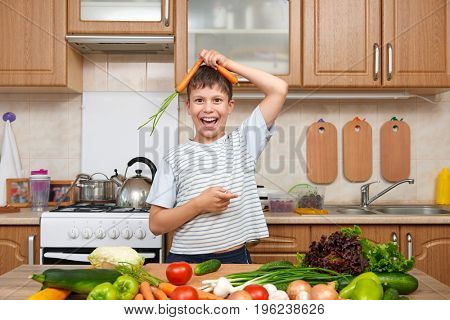 Child boy having fun with carrot. Home kitchen interior with fruits and vegetables. Healthy food concept