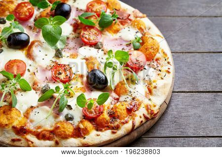 Pizza with ham, cherry tomatoes and mozzarella