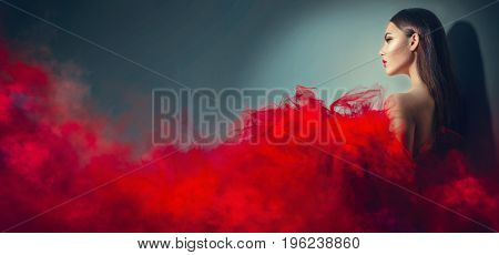 Beautiful High fashion woman in red dress posing in studio. Gorgeous brunette model girl with beautiful hairstyle and make-up, Wearing Stunning evening red dress with long gown of tulle and smoke