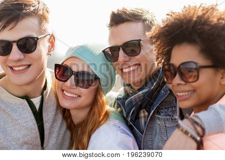 people, friendship and teenage concept - group of happy friends in sunglasses hugging and talking on city street