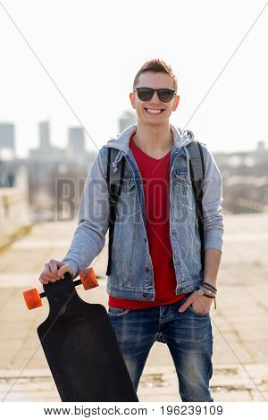 extreme sport and people concept - happy smiling young man or teenage boy with backpack and on longboard in city