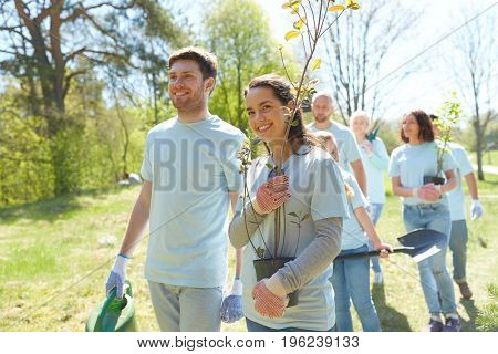 volunteering, charity, people and ecology concept - group of happy volunteers with tree seedlings and shovel walking in park