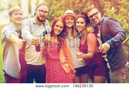 leisure, holidays, people, reunion and celebration concept - happy friends with drinks at summer garden party