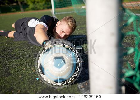 sport, technology and people - soccer player or goalkeeper lying with ball at football goal on field