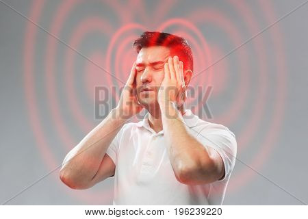 people, pain and stress concept - unhappy man suffering from head ache and touching his temples over gray background