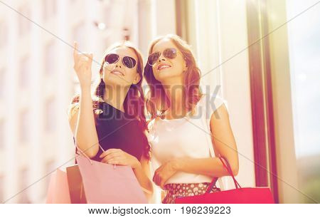 sale, consumerism and people concept - happy young women with shopping bags pointing finger outdoors