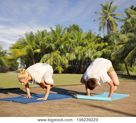 fitness, sport, yoga and people concept - couple making side crow pose on mat over natural background with palm trees