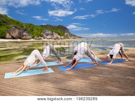 fitness, sport, yoga and healthy lifestyle concept - group of people making downward facing dog pose over exotic tropical beach background