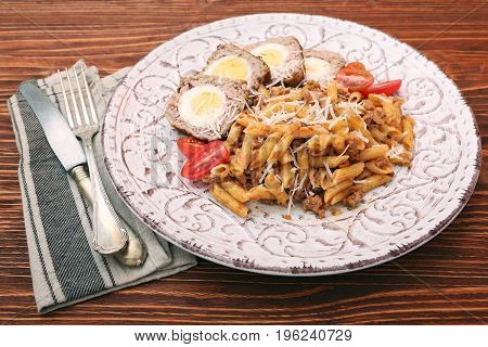 Boiled eggs in a layer of sausage meat wrapped with pasta on wooden background