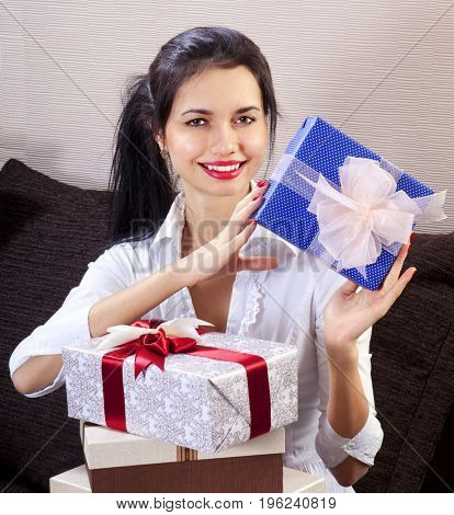 Young happy woman smiling and holds blue gift box in hands