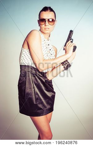 Beautiful woman assassin holding gun