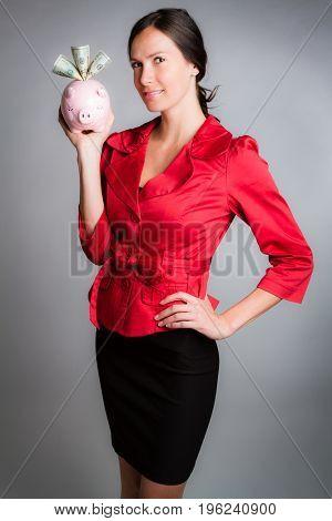 Beautiful businesswoman holding piggy bank