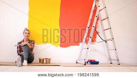 Portrait of a beautiful young female painter sitting on floor near wall after painting.