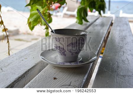 Cup of tea whit silver spoon at wooden bench