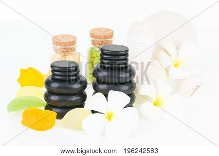 Spa with hot stones, bath salt, herbal compress balls and shell shaped soaps over white background