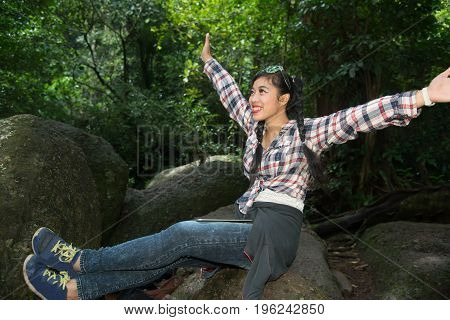 Pretty Asian traveler woman in happiness on a rock in forest.