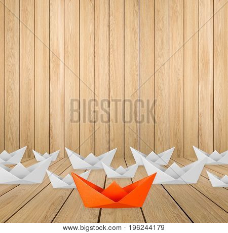 leadership concept with orange paper boat leading